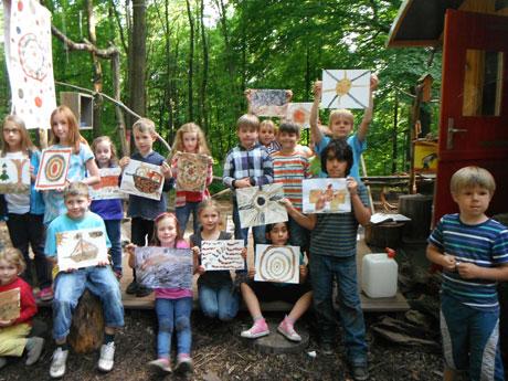 Nach einem kreativen Nachmittag präsentieren die Kinder stolz ihre mit Naturfarben gemalten Bilder.