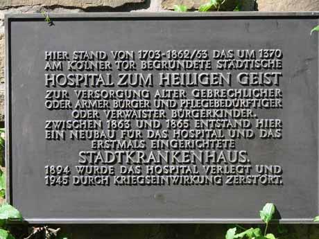 """ie Bronzetafel vor dem Eingang des ehemaligen """"Haus Siegen"""", die auf das 1703 an diesem Standort gegründete Hospital hinweist."""