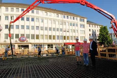 Bürgermeister Steffen Mues (r.) ließ sich vom Bauleiter der Firma Fritz Meyer, Björn Sahm (mitte), und von Stefan Engelhardt (l.) vom Planungsbüro BPR das Betonieren erklären.