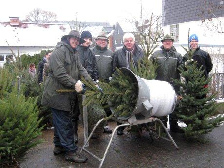 Thomas Otterbach (3.v.l.) verkauft mit seinem Vater (2.v.r.) seit 19 Jahren Weihnachtsbäume für einen guten Zweck. Schirmherr Landrat Paul Breuer (Mitte) hat sich seinen für dieses Jahr schon geholt. Foto: Kreis