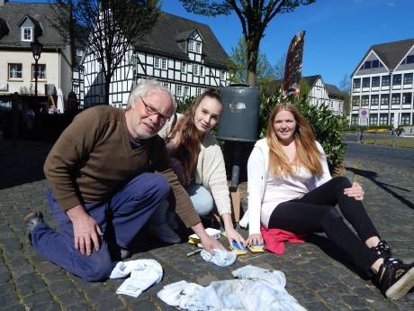 Melina Frick, Klaus Stötzel und Marlin Bald reinigen die Stolpersteine. Foto: Stadt
