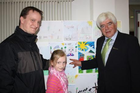 Lina Althaus mit ihrem Vater und Landrat Paul Breuer vor dem Bild, das sie für die Klimakonferenz gemalt hat. Foto: Kreis