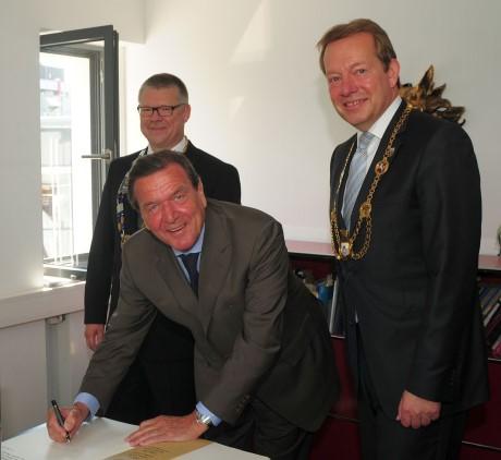 Altkanzler Gerhard Schröder ist der aktuellste Neuzugang im Goldenen Buch der Stadt Siegen. Bei seinem Eintrag wurde er flankiert von Dr. Martin Hill, Präsident des Rotary Clubs Siegen (li.) und Bürgermeister Steffen Mues. Foto: Stadt