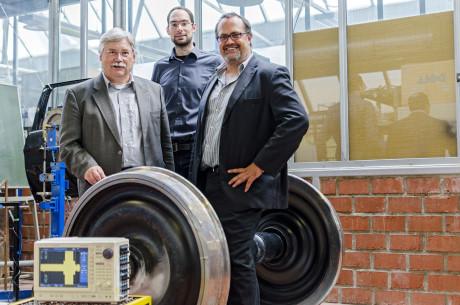 Prof. Dr.-Ing. Claus-Peter Fritzen, Henning Jung und Prof. Dr.-Ing. Peter Haring- Bolίvar präsentieren ein Drehgestell. Foto: Uni