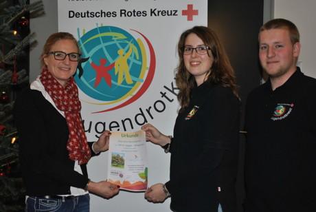 v.l.: Stadtmitarbeiterin Frau Ihlenfeld übergibt das Baumzertifikat an Melanie Graf und Maik Neeb vom Jugendrotkreuz (Foto: DRK)