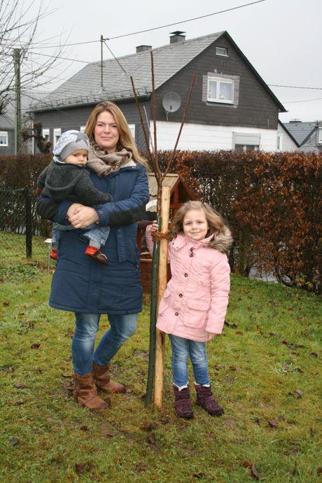 Frisch gepflanzt! Das Süßkirschenbäumchen für den kleinen Felix wird nun in Altenseelbach Wurzeln schlagen. Das freut auch Verena und Stella Meyer. Foto: Gemeinde