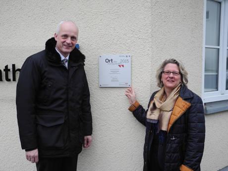 """An der Rathauswand hängt die Plakette """"Ort des Fortschritts"""", die Bürgermeister Christoph Ewers und NRW-Wissenschaftsministerin Svenja Schulze enthüllten."""