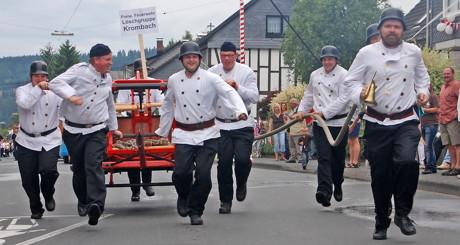 Feuerwehrkameraden in historischer Montur während eines Festzuges.