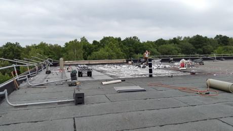 Ein Arbeitsplatz in luftigen Höhen. Bevor das Dach saniert und gedämmt werden kann, müssen die alten Baustoffe beseitigt werden.