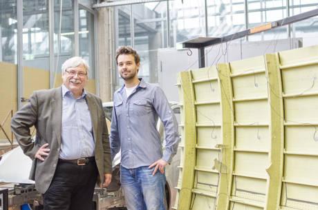 Prof. Claus-Peter Fritzen (l.) und Daniel Ginsberg neben einem Flugzeugbauteil mit Sensoren. (Foto: Uni)