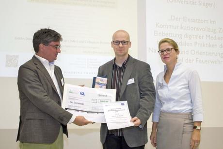 """Dr. Jan Gerwinski (Mitte) nimmt den Nachwuchspreis """"Berufliche Kommunikation"""" 2015 entgegen. Wie kommunizieren, wenn's brennt? (Foto: Uni)"""