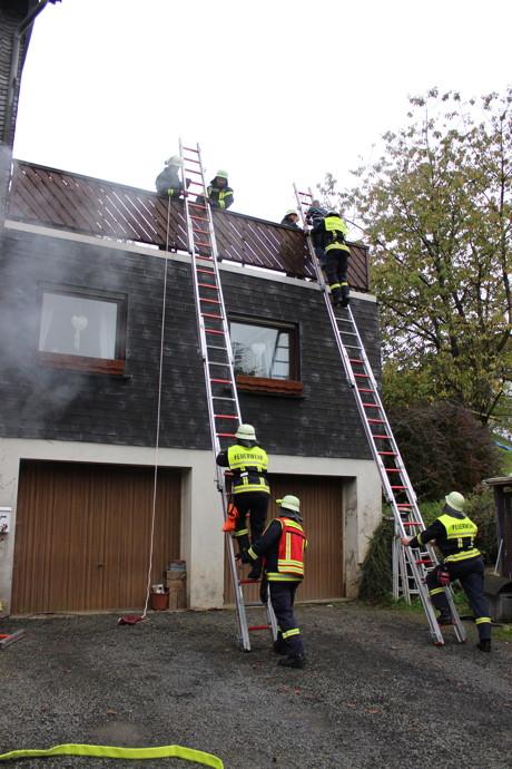 Über Steckleitern werden die Personen über den Balkon gerettet.