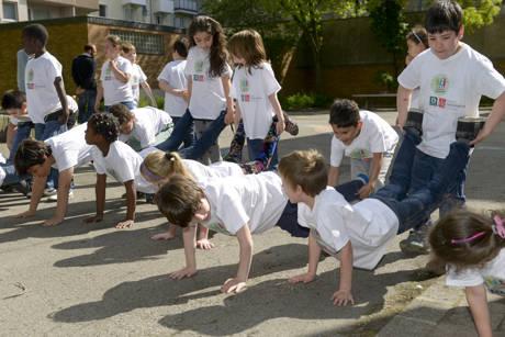 """Grundschüler liefern sich ein """"Formel eins""""-Schubkarren-Rennen auf dem Pausenhof."""