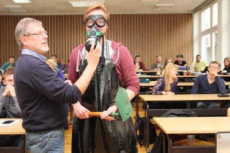 Fahrer von Gefahrgütern müssen eine Schutzausrüstung mit sich führen. Gefahrgutausbilder Wolfgang Sonntag hilft beim Anlegen der Schutzkleidung. (Foto: Berufskolleg)