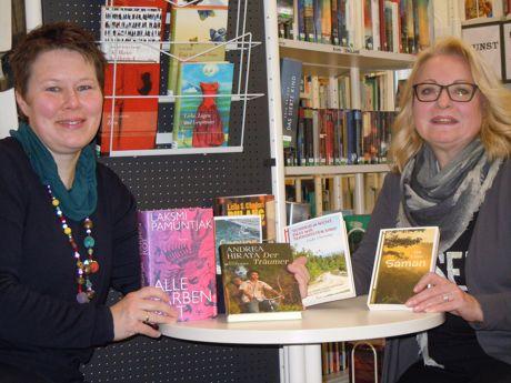 """Monika Schröder (links) von der Buchhandlung MankelMuth überreicht Büchereileiterin Gabriele Klotz die signierten Exemplare der Literaturpflaster Autoren """"Indonesien""""."""