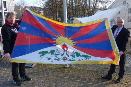 Bürgermeister Holger Menzel und sein Mitarbeiter Karsten Valenta (links) präsentieren vor dem Hissen die Flagge Tibets am Marktplatz. Foto: Stadt Hilchenbach
