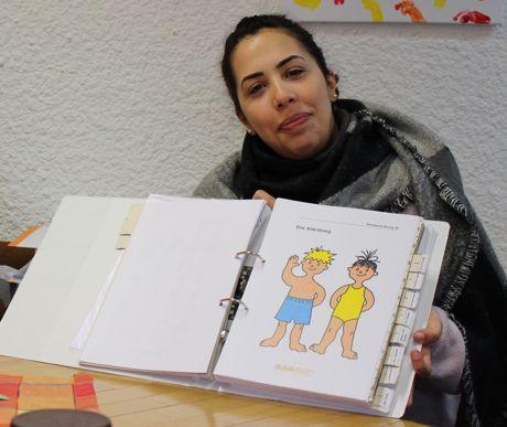 """Elternbegleiterin Mariem Benoufella mit Materialien des Programms """"Rucksack KiTa""""."""