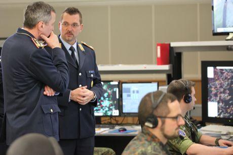 Generalleutnant Joachim Wundrak (l.), wird im Control- and Reporting Center des Einsatzführungsbereich 2 durch den Einsatzstabsoffizier, Major Thorsten Thielke (2.v.l.), informiert.
