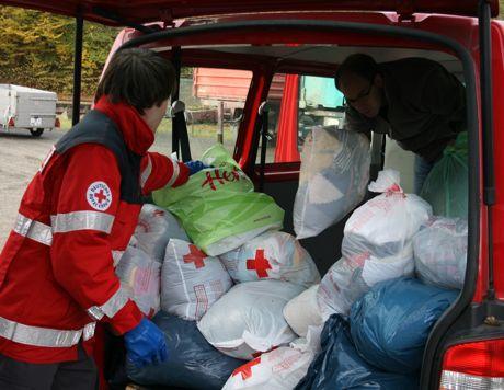 DRK-Helfer sammeln die Kleidersäcke am Straßenrand ein.