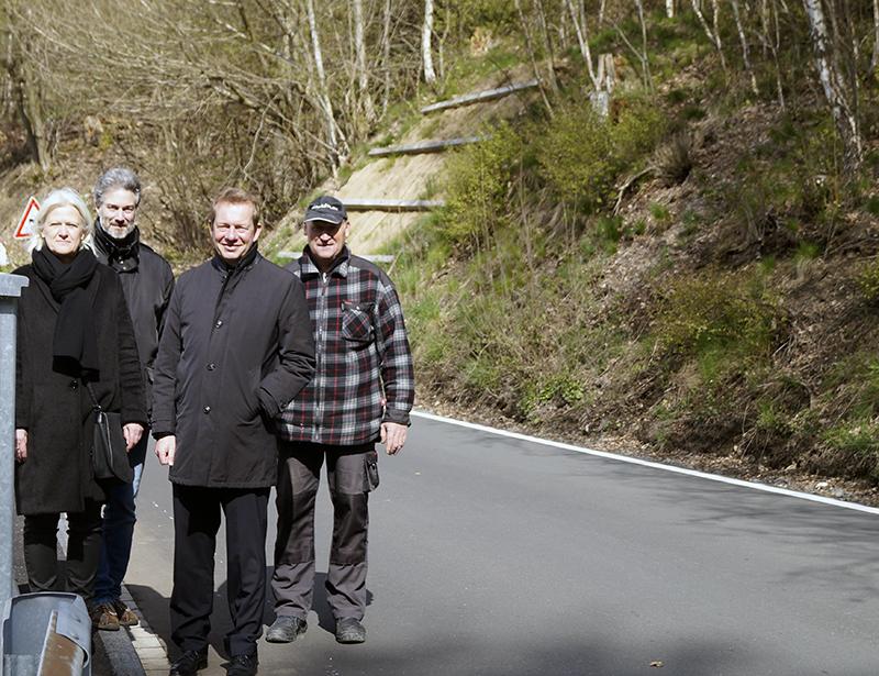 Helge Klinkert (Kreisdezernetin Straßenbau), Oliver Alt (Projektleiter Straßen.NRW), Bürgermeister Steffen Mues und Jörg Ottersbach (Schachtmeister Firma Fink-Stauf) auf der sanierten Straße.