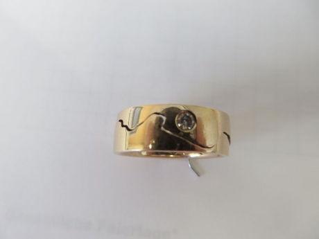 """Bei dem Ring handelt es sich um einen goldenen, teilbaren Ehering mit eingearbeitetem Brillant. Auf der Innenseite sind der Name """"Kans"""" oder """"Hans"""" und das Datum """"21. Juni 14"""" eingraviert."""