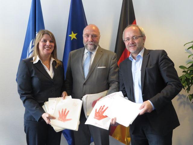 """Christa Schuppler und Volkmar Klein übergeben """"rote Hände"""" an Günter Nooke, den Afrikabeauftragten der Bundeskanzlerin in Berlin. (Foto: CDU)"""