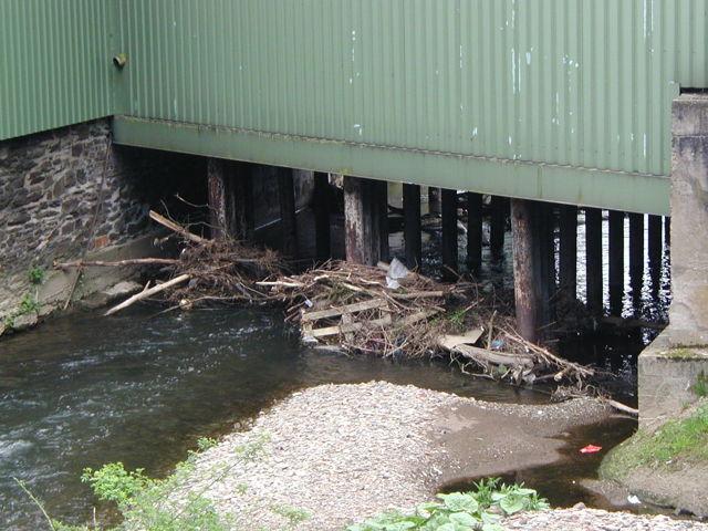 Wenn Ablagerungen wie Gartenabfälle oder Gehölzschnitt abgeschwemmt werden und anschließend an Brücken o.ä. hängen bleiben, verengen sie das Abflussprofil des Gewässers. Die Folge: Das Gewässer tritt schneller über die Ufer. (Foto: Stadt Siegen)
