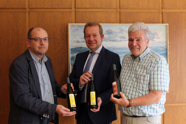 Die Vorstandsmitglieder des Siegerländer Weinkonvents, Michael Dickel (links) und Wolfgang Narjes (rechts), überreichten Bürgermeister Steffen Mues Wein aus heimischem Anbau. Die Stadt Siegen gibt die raren Tropfen als besondere Geschenke weiter. (Foto: Stadt Siegen)