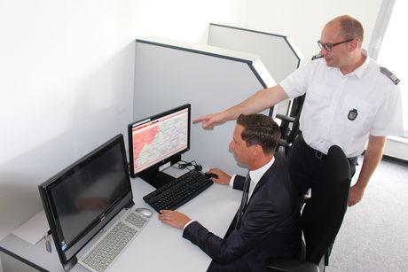 Thomas Jung (r.), Leiter der Kreisleitstelle, erläutert Landrat Andreas Müller die MoWaS-Software, mit der auch die App NINA angesteuert werden kann.